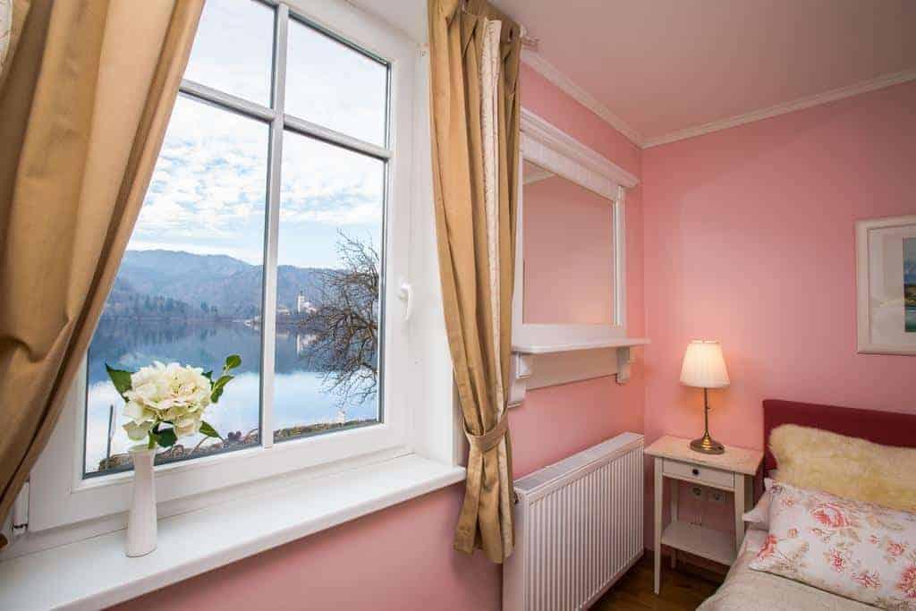 غرفة نوم و نافذة تطل على بحيرة بليد في فندق كارمان جيست هاوس
