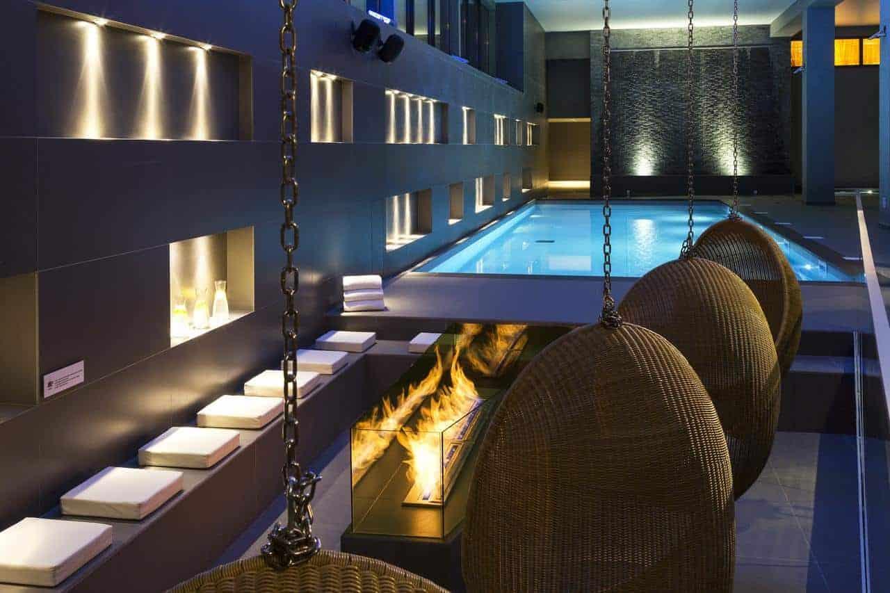كراسي متدلية أمام المسبح في فندق آند سبا لو هليوتك سويت